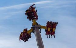 Gente que monta arriba en el aire en un paseo del festival del carnaval contra el cielo azul Fotos de archivo