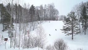 Gente que monta cuesta abajo cerca de pequeño Ski Lift almacen de metraje de vídeo