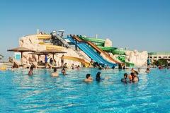 Gente que nada en el hotel de la piscina del parque del agua en Hurghada Egipto Foto de archivo libre de regalías