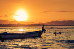 Gente que nada en la playa en Puerto Viejo de Talamanca, Costa Rica, en la puesta del sol Fotografía de archivo libre de regalías