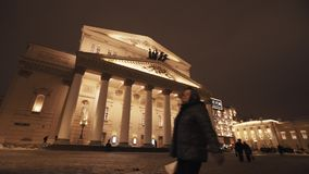 Gente que pasa cerca delante del edificio del teatro el noche del invierno almacen de metraje de vídeo