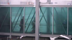 Gente que pasa a través del puente del jet del avión al aeropuerto metrajes