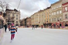 Gente que patina en una pista de patinaje de la ciudad, sonrisa alegre de la muchacha Imagen de archivo libre de regalías