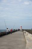 Gente que pesca delante del faro Imagen de archivo libre de regalías