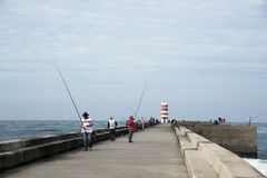 Gente que pesca delante del faro Imágenes de archivo libres de regalías
