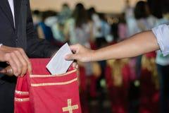 Gente que pone tithing en bolso de ofrecimiento del terciopelo en iglesia Fotos de archivo libres de regalías