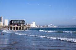 Gente que practica surf y que nada en el mar en Durban Foto de archivo