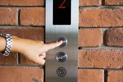 Gente que presiona el botón del elevador Fotos de archivo libres de regalías