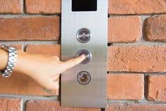 Gente que presiona el botón del elevador Imágenes de archivo libres de regalías