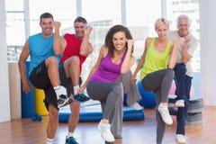Gente que realiza ejercicio de los aeróbicos en clase del gimnasio Imágenes de archivo libres de regalías