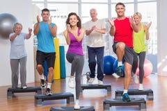Gente que realiza ejercicio de los aeróbicos del paso en gimnasio Fotografía de archivo