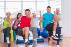 Gente que realiza ejercicio de los aeróbicos en clase del gimnasio Fotografía de archivo