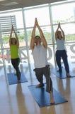 Gente que realiza yoga en la estera Fotos de archivo