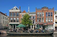 Gente que reconstruye en terraza soleada del barco en Leiden Foto de archivo