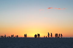 Gente que recorre en la puesta del sol Fotografía de archivo