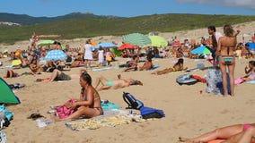 Gente que relaja, tomando el sol y jugando a los juegos en la playa, actividades del verano metrajes