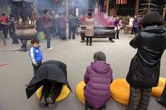 Gente que ruega a Buddha en templo Foto de archivo libre de regalías