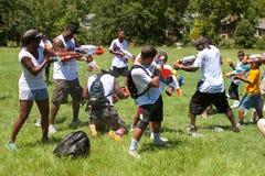 Gente que se arroja a chorros en lucha del arma de agua Fotos de archivo