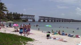 Gente que se baña en Bahia Honda con el puente del ferrocarril en fondo almacen de video