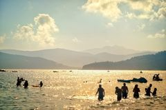 Gente que se baña en el mar en la puesta del sol imágenes de archivo libres de regalías