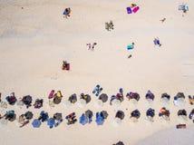 Gente que se baña en el sol en la playa Turistas en una playa de la arena Imagen de archivo