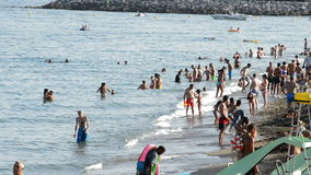 Gente que se baña en una playa mediterránea en la puesta del sol metrajes