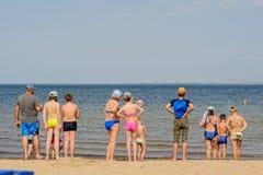 Gente que se coloca en la arena cerca del mar Fotos de archivo libres de regalías
