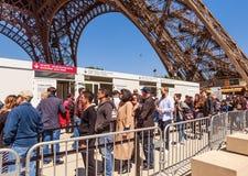 Gente que se coloca en la cola para control para conseguir en el territorio de la torre Eiffel fotografía de archivo