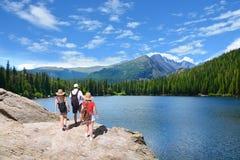 Gente que se coloca encima de la montaña que mira paisaje hermoso Fotos de archivo libres de regalías