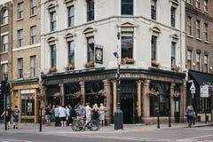 Gente que se coloca y que bebe fuera del pub de diez Belces en Shoreditch, Londres, Reino Unido foto de archivo libre de regalías