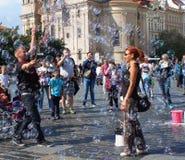 Gente que se divierte con las burbujas de jabón en la vieja plaza en Praga Foto de archivo