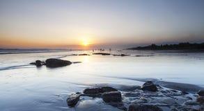 Gente que se divierte en la playa en la puesta del sol Foto de archivo