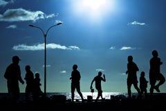 Gente que se ejecuta en la puesta del sol Imágenes de archivo libres de regalías