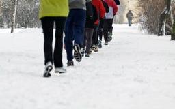 Gente que se ejecuta en parque del invierno imagen de archivo