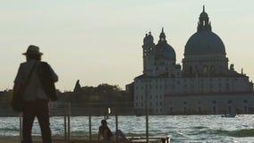 Gente que se enfría en el embarcadero, golpe por las aguas picadas del río con la catedral a través de ella metrajes