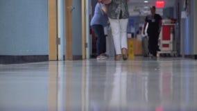 Gente que se mueve alrededor en un vestíbulo ocupado del hospital metrajes
