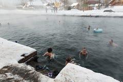 Gente que se relaja en balneario geotérmico público en piscina de las aguas termales Foto de archivo