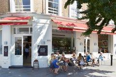 Gente que se relaja en tablas al aire libre, cerca del café en Londres Fotos de archivo libres de regalías