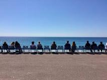 Gente que se sienta al lado del mar Imagenes de archivo