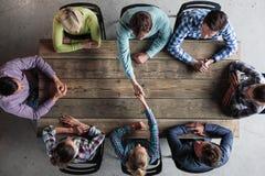 Gente que se sienta alrededor de la tabla que da el alto cinco foto de archivo