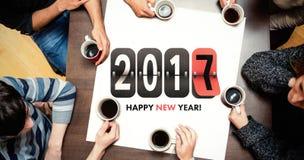 Gente que se sienta alrededor del café de consumición de la tabla contra gráfico del Año Nuevo fotografía de archivo libre de regalías