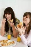 Gente que se sienta comiendo la pizza Imagenes de archivo