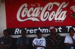 Gente que se sienta debajo de una muestra de publicidad, Uganda Fotografía de archivo libre de regalías