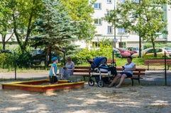Gente que se sienta en banco Foto de archivo