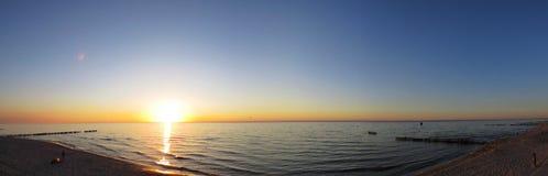 Gente que se sienta en banco en la playa de la playa de la arena durante puesta del sol con las nubes foto de archivo