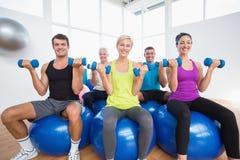 Gente que se sienta en bolas y pesos de elevación en club de fitness Imágenes de archivo libres de regalías