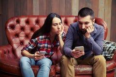 Gente que se sienta en el sofá y que mira el teléfono fotografía de archivo