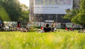 Gente que se sienta en hierba Foto de archivo libre de regalías