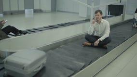 Gente que se sienta en la banda transportadora en el aeropuerto metrajes
