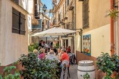 Gente que se sienta en la barra exterior en una calle estrecha en el centro histórico de Monreale Fotografía de archivo